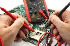 Digitalmessinstrument mit Sonde in den Meister-` s Händen in einer Werkstatt Stockbilder