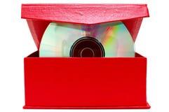 Digitalschallplatte (CD oder DVD) und roter Sammelpack. stockfotografie