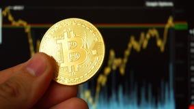 Digitalt BTC Bitcoin mynt för handinnehav på framdel av diagram fotografering för bildbyråer