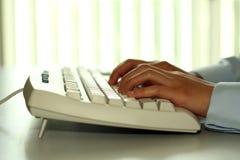 Digitando su una tastiera fotografie stock