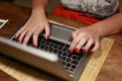 Digitando su una tastiera del computer portatile Fotografia Stock