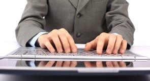 digitando sul suo computer portatile. Fotografia Stock