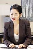 Digitare abbastanza asiatico della donna di affari Fotografie Stock