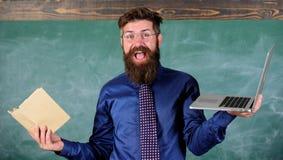 Digitas contra o papel Escolha o método de ensino direito Professor que escolhe a aproximação moderna do ensino Tecnologias moder fotos de stock