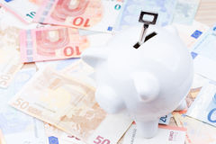 Digiti un porcellino salvadanaio sulle banconote Fotografie Stock