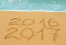 Digits 2016 and 2017 on the sand. Digits 2016 and 2017 on the beach - concept of new year and passing of time royalty free stock image
