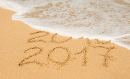 Digits  2016 and 2017 on the sand. Digits  2016 and 2017 on the beach sand - concept of new year,vacation,travel  and passing of time Royalty Free Stock Images