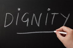 Dignity. Hand writing the word Dignity on a blackboard. Being treated with dignity is important to us irrespective of age,gender or physical and mental ability royalty free stock photos