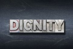 Dignity word den. Dignity word made from metallic letterpress on dark jeans background stock image