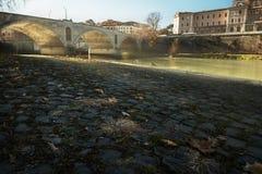 Dijk van de rivier bij de brug in de vroege ochtend rome stock foto