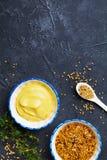 Dijon mustard and french mustard on black stone background top view. Dijon mustard and french mustard on stone background top view stock photography
