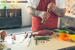 Dik kerel peppering vlees alvorens te koken stock afbeelding