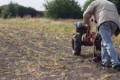 DIKANKA, ΟΥΚΡΑΝΙΑ - 30 ΣΕΠΤΕΜΒΡΊΟΥ 2015: Ο αγρότης χώρας οργώνει τον κήπο του με το περίπατος-πίσω τρακτέρ κήπων Στοκ Εικόνες