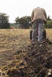 DIKANKA, ΟΥΚΡΑΝΙΑ - 30 ΣΕΠΤΕΜΒΡΊΟΥ 2015: Ο αγρότης χώρας οργώνει τον κήπο του με το περίπατος-πίσω τρακτέρ κήπων Στοκ Εικόνα
