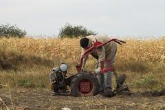 DIKANKA, ΟΥΚΡΑΝΙΑ - 30 ΣΕΠΤΕΜΒΡΊΟΥ 2015: Ο αγρότης χώρας οργώνει τον κήπο του με το περίπατος-πίσω τρακτέρ κήπων Στοκ Φωτογραφία