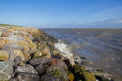 Dike with boulders. Solid dike in the Netherlands, boulders used for toe protection stock photography