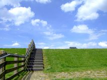 Dike in Holland. A sea dike in the Netherlands and a blue sky with small clouds Royalty Free Stock Photo