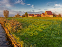 Dike houses and polder, Eemdijk, Holland. Dutch polder landscape with farm houses on dike of river Eem, Netherlands Royalty Free Stock Images