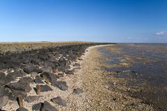Dike at ebb tide. Dike in the Netherlands at ebb tide, boulders used for toe protection stock images