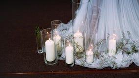 Dikke brandende kaarsen die zich in transparante die vazen bevinden door textiel worden omringd stock videobeelden