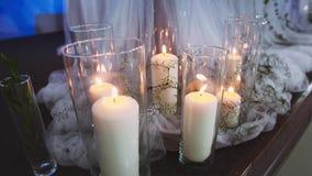Dikke brandende kaarsen die zich in transparante die vazen bevinden door textiel worden omringd door een discolicht wordt aangest stock video