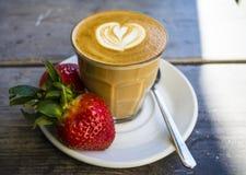 Dikke glastuimelschakelaar met cappuccino en latte-kunst in het vormhart Verse aardbei en koffie Op hout met schotel, lepel stock afbeelding