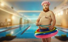 Dikke grappige mens in de opblaasbare cirkel in de pool Stock Foto's