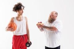 Dikke kerel die dunne sportman verleiden door cake Stock Fotografie
