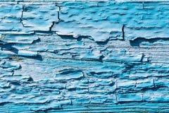 Dikke laag van blauwe gebarsten verf op de raad stock foto's