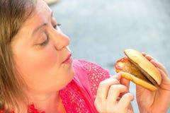 Dikke vrouw die snel voedselhamburger en frieten in caf eten Stock Foto