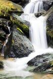 Dikke zachte krachtige waterval tussen stenen Royalty-vrije Stock Fotografie