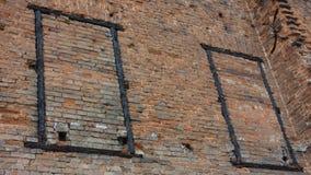 Dilapidated bakstenen muur met twee brandwond uit raamkozijnen royalty-vrije stock afbeeldingen