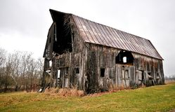 Dilapidated barn. Side view of a severely dilapidated barn in a country setting Royalty Free Stock Photography
