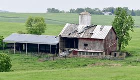 Dilapidated Barn in Dane County. This is a Summer picture on a hot, humid, hazy day of a dilapidated dairy barn in a valley located in Dane County, Wisconsin royalty free stock photography