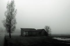 Dilapidated barn in fog. Dilapidated, rundown barn in a soggy field in dense fog royalty free stock photos