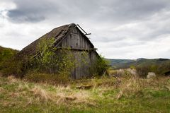 Dilapidated barn overgrown by shrubs and trees. Rural West Slovakia countryside with abandoned barn and farmland Royalty Free Stock Images