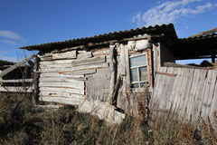 Dilapidated barrack. Tumbledown hut built from scrap items Stock Image