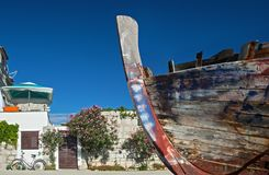 Dilapidated boat hull against blue sky. Decaying, colorful, wooden boat hull against blue sky with house, oleander shrubs and bicycle in the background royalty free stock images