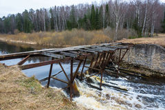 The dilapidated bridge over the small tumultuous river. Royalty Free Stock Photo