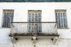Dilapidated Building Facade. Dilapidated white building facade, flaking blue painted shutters, rusted metal balcony Royalty Free Stock Photos