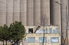 Dilapidated Building and Grain Storage Silos Stock Photo