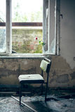 Dilapidated chair by the window Stock Image