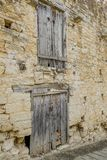 Two sets of very old wooden doors in a stone wall. Dilapidated closed wooden doors in an ancient stone wall Royalty Free Stock Photography