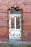 Dilapidated door in masonry house front Royalty Free Stock Images