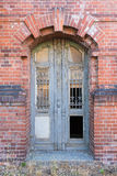 Dilapidated door in masonry house front Royalty Free Stock Photo