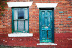 Dilapidated door and window. A view of a blue door and window on the side of a dilapidated old brick building Stock Photo