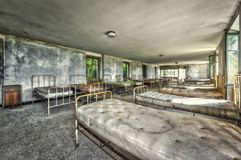 Dilapidated dormitory in an abandoned children hospital. HDR processing royalty free stock images