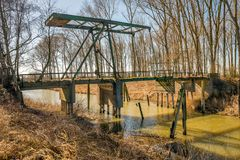 Dilapidated drawbridge over a river. Dilapidated drawbridge over a narrow Dutch river. The bridge was built in 1929 and used to 1962. Since then, the bridge has Stock Photo