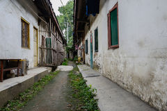 Dilapidated dwelling buildings along unpaved alley Royalty Free Stock Images