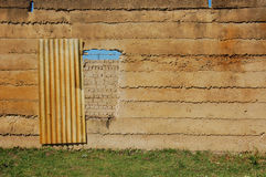 Dilapidated Entrance. Concrete wall with make shift door Royalty Free Stock Image